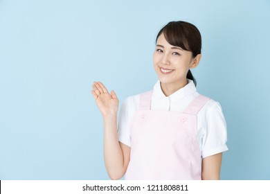 portrait of young asian nurse wearing apron on blue background
