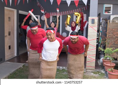 portrait of young asian people compete sack race during indonesia independence day