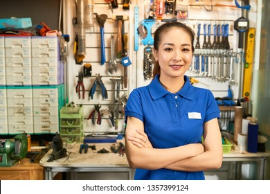 Portrait of young Asian saleswoman standing with arms crossed and looking at camera with wall with instruments in the background