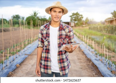 Portrait of young Asian smart farmer holding tablet in his organic farm. Technology and agriculture concept