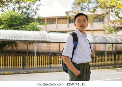portrait of a young asian student in standard uniform, chinese ethnicity, standing near the school compound, looking towards future, thinking of his ambition. concept of education with copy space