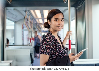 Portrait of a young Asian student using her cellphone while riding on a train in the city during her morning commute