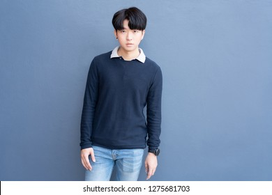 Portrait of Young Asian teenage cool hair stylish wearing blue sweater indicate blank space on blue navy wall background.