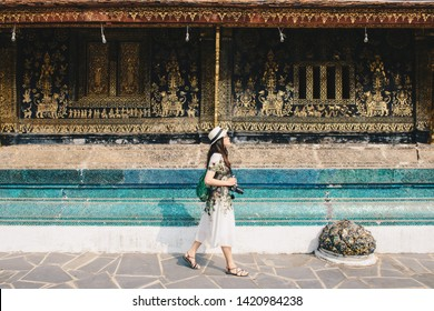 Portrait of young Asian tourist visiting Wat Xieng Thong an iconic temple in Luang Prabang, the UNESCO world heritage town in north central of Laos. Conceptual of tourist enjoying vacation and holiday
