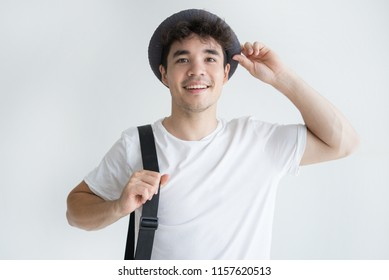 Portrait of young Asian tourist wearing sunhat and carrying bag looking at camera and smiling. Travel and tourism concept
