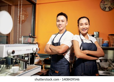 Portrait of young Asian waiter and waitress standing in uniform with arms crossed and smiling at camera near the coffee machine in coffee shop