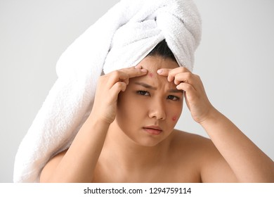 Portrait of young Asian woman with acne problem squishing pimples on white background
