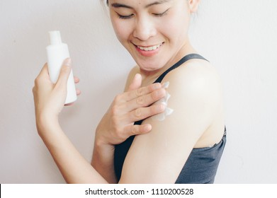 Portrait of young Asian woman applying sunscreen lotion on her body for protect her skin.