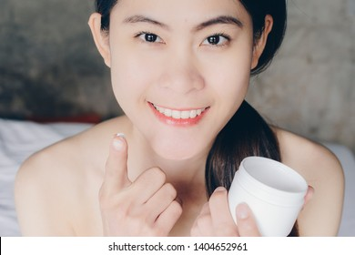 Portrait of young Asian woman applying acne cream/moisturizer on her face. Conceptual of beauty and cosmetic.