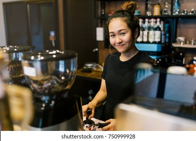Portrait of a young Asian woman Barista preparing cappuccino with machine at coffee shop.