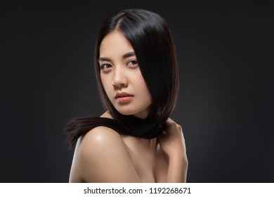 portrait of young asian woman with beautiful and healthy dark hair posing isolated on black
