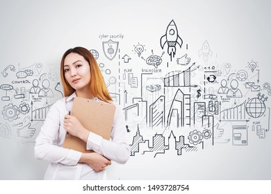 Portrait of young Asian woman with clipboard standing near white wall with business plan sketch drawn on it. Concept of business strategy