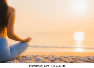Portrait young asian woman do meditation around sea beach ocean at sunrise for health