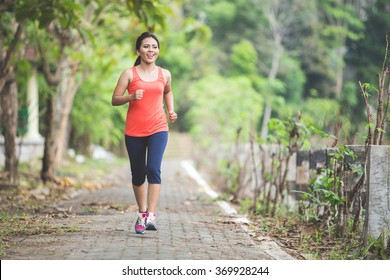 A portrait of a young asian woman doing exercise outdoor in a park, jogging
