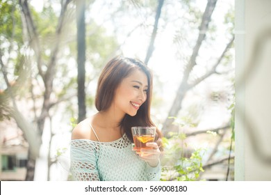 Portrait of a young asian woman drinking her morning tea. Fell relaxed.