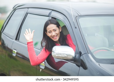 A portrait of a young Asian woman driving a car, waving her hand out of the window