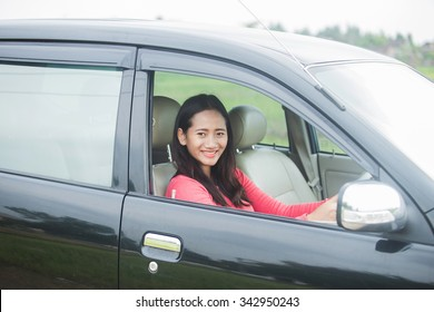 A portrait of a young Asian woman driving a car, smiling to the camera