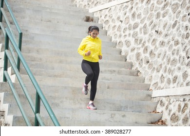 A portrait of a Young asian woman exercising outdoor in yellow jacket, jogging going up and down the stair