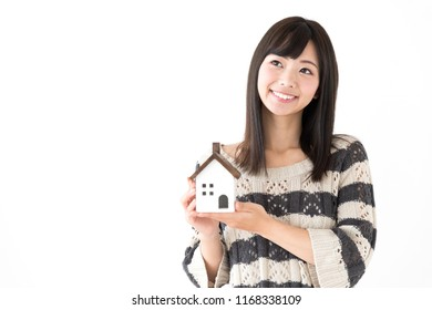 portrait of young asian woman holding miniture house on white background