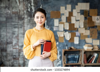 Portrait of a young asian woman holding books.