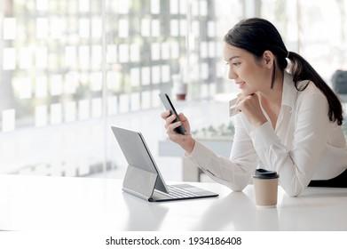 Porträt junger asiatischer Frauen, die während ihrer Arbeit am Schreibtisch Smartphone und Kreditkarte halten.