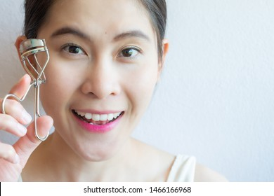 Portrait of young Asian woman looking to camera and holding eyelash curler. Eyelash curler is a hand-operated mechanical device for curling eyelashes for cosmetic purposes.