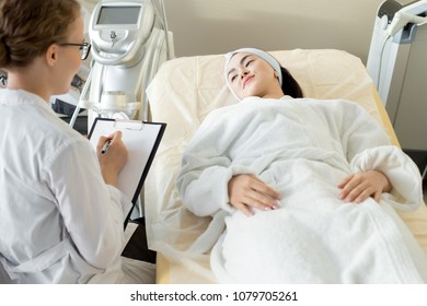 Portrait of young Asian woman lying on massage table and listening to cosmetologist giving instructions for treatment