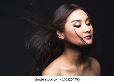 Portrait of young asian woman with makeup long hair on the black isolated posing.