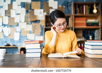 Portrait of a young asian woman reading a book.