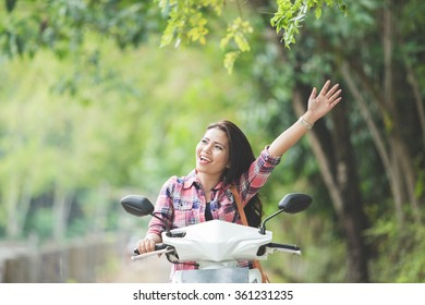 A portrait of a young asian woman riding a motorcycle on a park, hand up