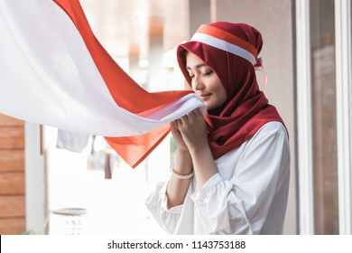 portrait of young asian woman with scarf kissing red and white flag of indonesia
