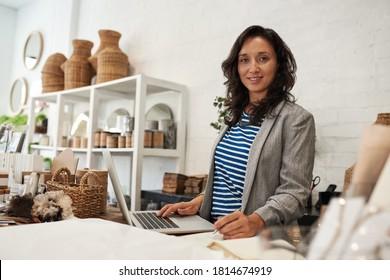 Porträt einer jungen Asiatin, die in ihrem Geschäft mit Noten und einem Laptop hinter der Theke lächelt