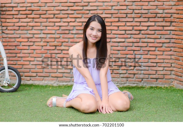 Portrait of young asian woman with smiling pretty sit on grass and brick wallpaper.