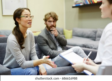 Portrait of young Asian woman talking to psychiatrist during couples counseling session with her husband