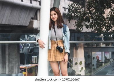 Portrait of young Asian woman tourist leaning against a pole outdoors in urban. Travel and vacation concept.