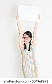 Portrait of young Asian woman in traditional qipao dress hand holding white blank paper card, celebrating Chinese Lunar New Year or spring festival, standing on plain background.