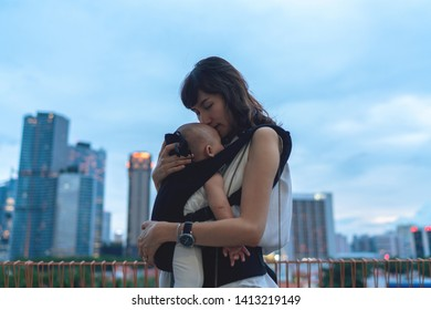 Portrait of young asian woman traveling with baby in Singapore against city skyline