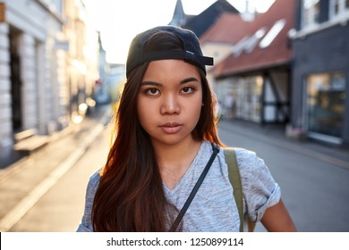 Portrait of a young Asian woman with an urban style and attitude walking along city streets in the late afternoon