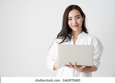 portrait of young asian woman using laptop on white background