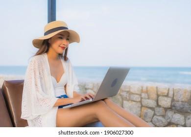 Portrait junge Asiatin, die einen Laptop für die Arbeit am Strand verwendet