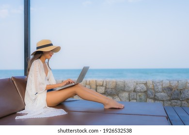 Portrait young asian woman using laptop computer for work around beach sea ocean