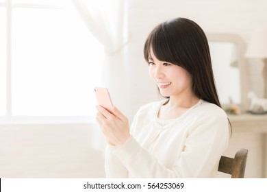 portrait of young asian woman using smart phone in the living room