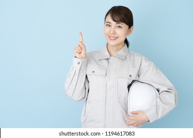 portrait of young asian woman wearing working clothes on blue background