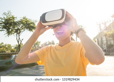 Portrait of young Asian woman wearing virtual reality goggles and enjoying the VR simulation experience. Conceptual of VR reality technology.