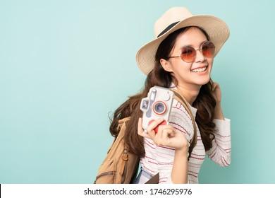 Porträt einer jungen asiatischen Frau, die eine Sonnenbrille und einen Hut trägt, die eine Kamera auf blauem Hintergrund trägt. Glückliche Menschen und Reisekonzept.