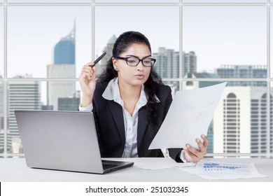 Portrait of young asian woman working in the office while reading a paperwork