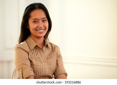 Portrait of a young asiatic woman on brown blouse smiling at you on closeup background - copyspace