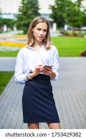 Portrait of a young assistant in a white blouse phoning on the street
