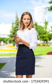 Portrait of a young assistant in a white blouse and with a phone in her hands posing outdoors