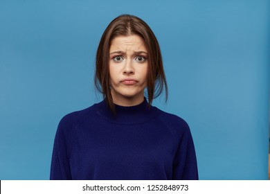portrait of young astonished female, dressed casualy, pressed her lips and feels upset about something. Isolated over blue background